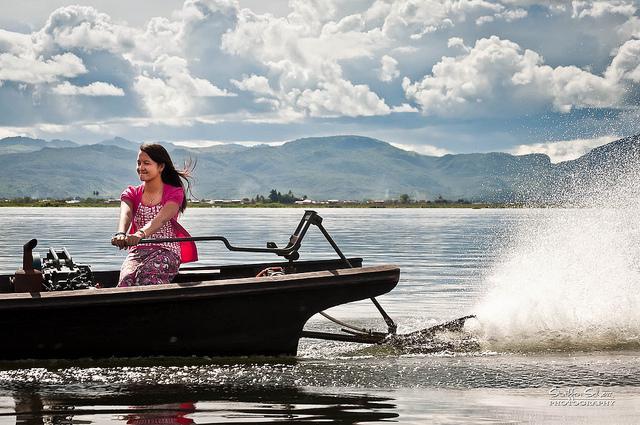 Een jonge vrouw zit aan het roer van een bootje en vaart over het grote meer.