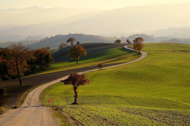 Tussen grasgroene heuvels kronkelt een klein baantje.