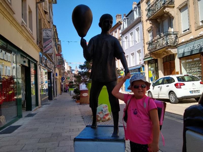 Dochtertje poseert bij een standbeeld in Sarrebourg