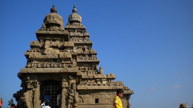 Een jongetje loopt voorbij de twee torens van de kunstig uit steen gehouwen tempel.