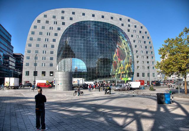 De markthal, een gebouw uit 2014, heeft een hoefijzer-vorm. Binnen zien we een glimp van een kleurig kunstwerk.