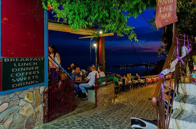 Een mooie avond, met mensen op een terrasje langs de kust.