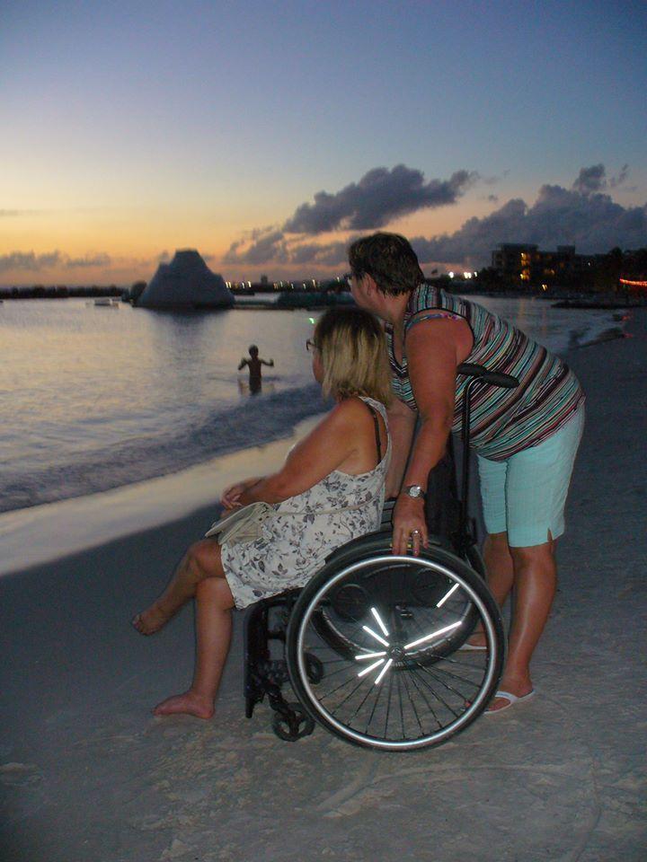 Nadine (met rolstoel) en Lia bij zonsondergang op het strand.