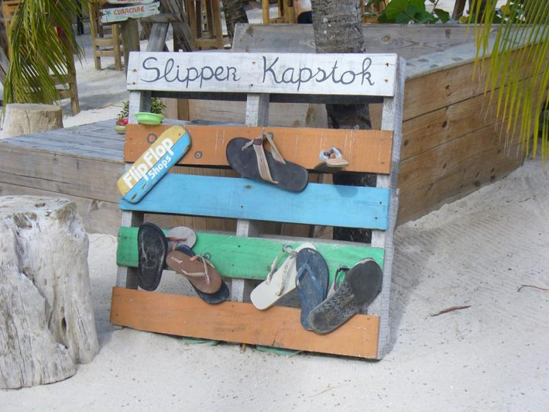 """Een houten palet is omgetoverd tot een kleurige """"slipperkapstok"""", voor wie blootvoets het strand op wil."""
