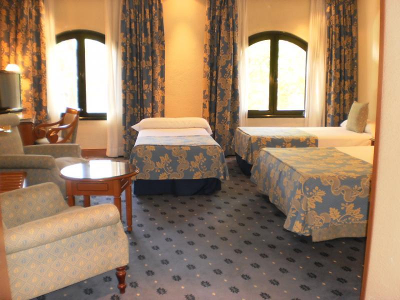 Suite met twee ramen, een 2-persoonsbed, twee 1-persoonsbedden en zithoek.