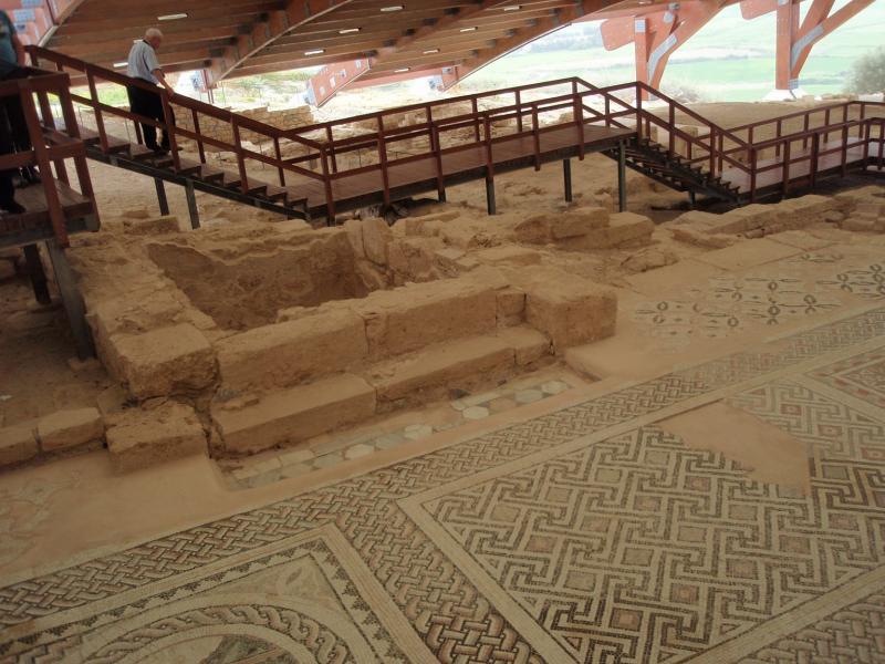 Archeologische site: een brug met trappen en borstwering loopt boven de antieke mozaïekvloeren.