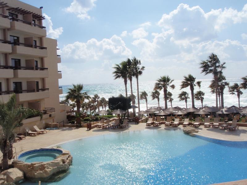 Uitzicht van het hotel, over het zwembad en de palmbomen.
