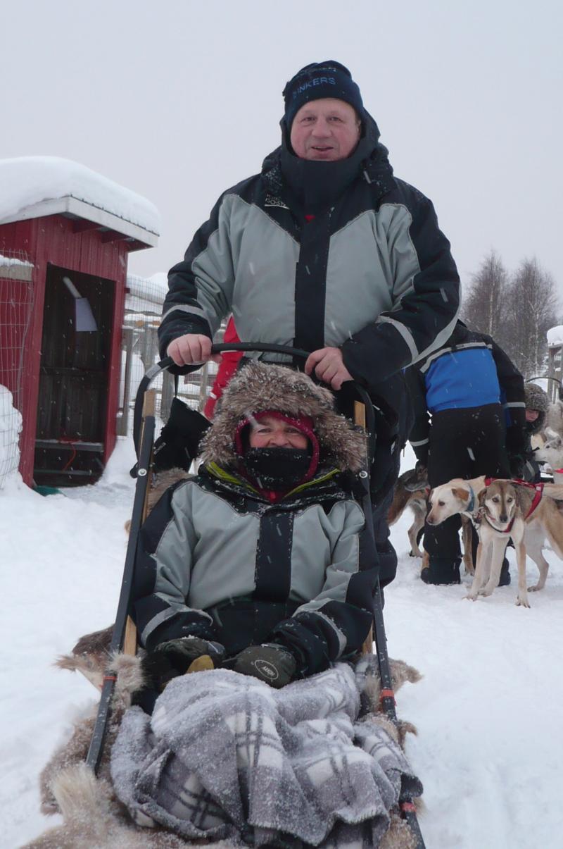 Goed ingeduffeld op de slee, met enkele honden op de achtergrond.