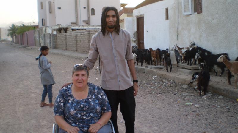 Pia en een reisgezel op een stoffige straat, tussen witte huizen. Op de achtergrond hoedt een meisje een kudde geiten.