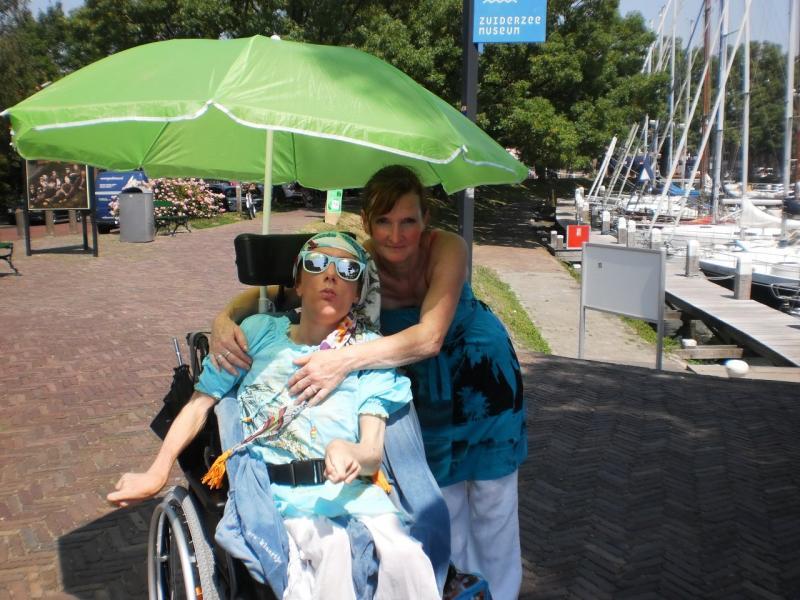 Klaartje en Heidi, moeder en dochter, genieten van de schaduw onder een parasol.