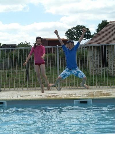 Twee kinderen springen uitgelaten in het water.