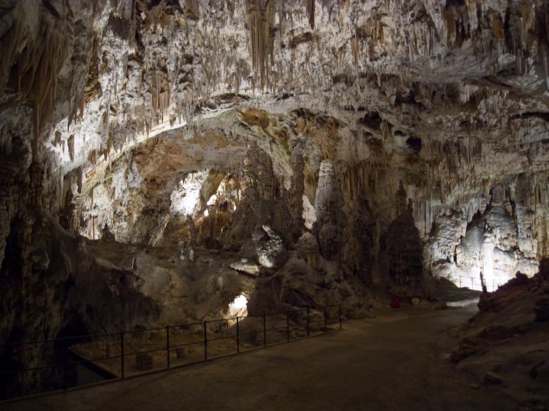 Een breed effen pad leidt bezoekers door de sfeervol verlichte grot.