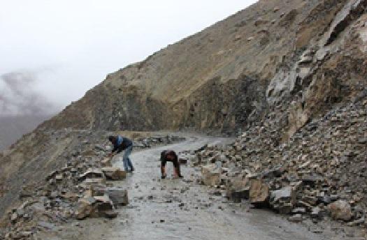 Twee mannen halen dikke stenen weg om de baan vrij te maken