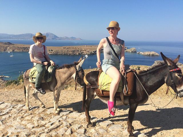 Twee vrouwen (niet Monique) rijden met de ezel door een rotsig landschap, met de zee op de achtergrond.