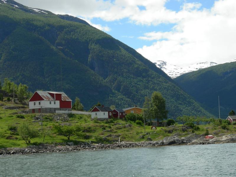 Noors dorpje tussen de heuvels, gefotografeerd vanaf een overzetboot.