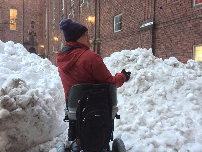 Rik met zijn scootmobiel midden in de sneeuw, die tot op ooghoogte komt.