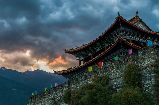 Donderwolken boven de bergen en een boeddhistisch klooster.