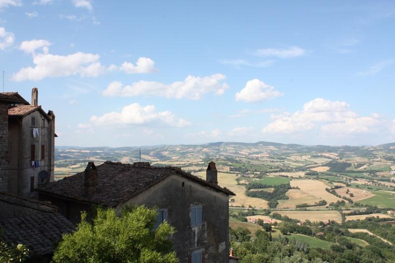 Typisch landschap in Umbrië: glooiende groene heuvels onder een stralende hemel. Op de voorgrond enkele eenvoudige huisjes.