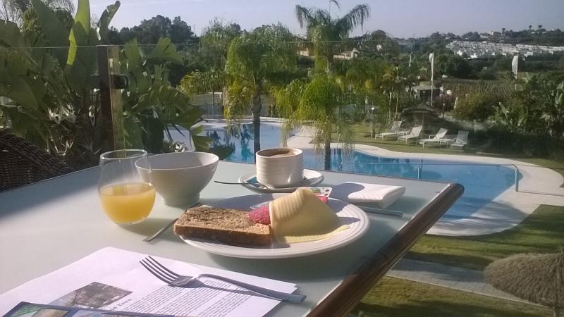 Ontbijt op het terras, met uitzicht op het zwembad.