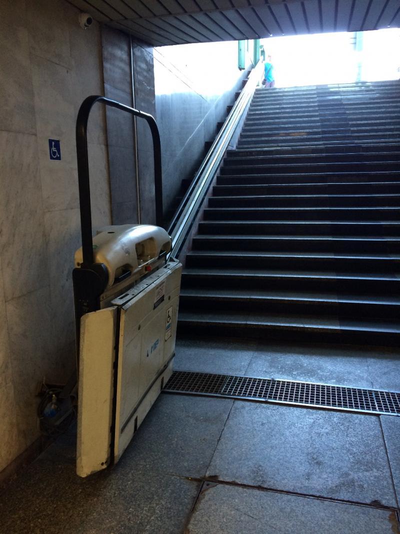 Trap met links een elektrische platform voor rolstoelers.