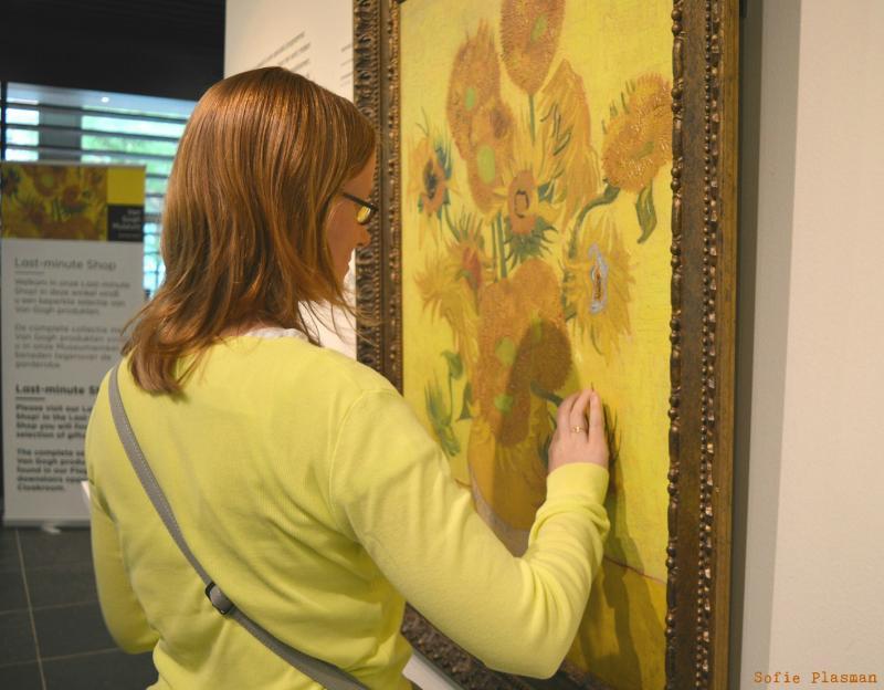 Karmen betast een kopie van het schilderij De Zonnebloemen. (foto Sofie Plasman)