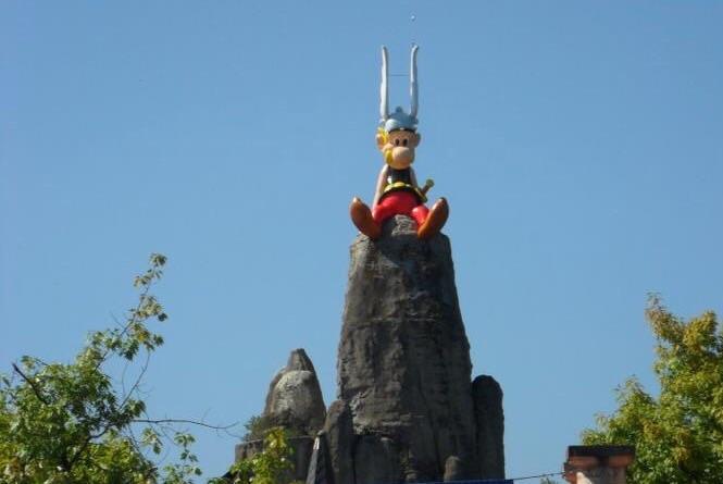 Asterix kijkt gezeten op een reuze menhir over het park.