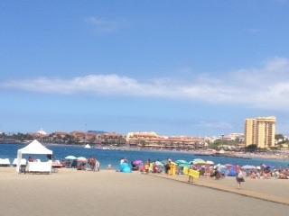 Het uitzicht vanop het terras met strand, zee en horeca.