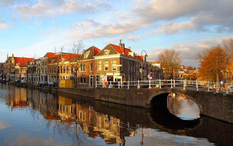 Een winterse foto van Delft. Het pittoreske stadje wordt weerspiegeld in het water van de Schie.
