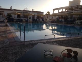 Het zwembad en hotel bij zonsondergang.