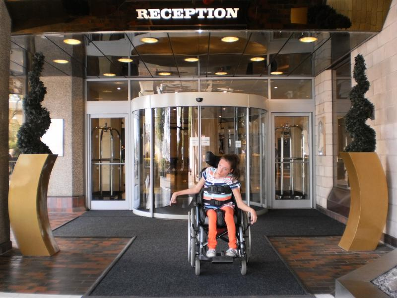 De ingang (met het woord Reception erboven) loopt langs een draaideur, geflankeerd door twee gewone glazen deuren.