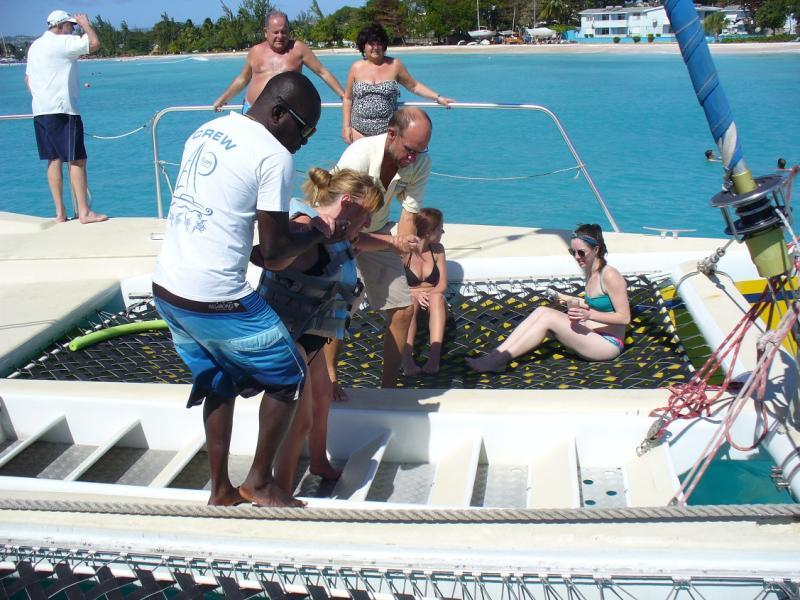 Nadine wordt van op de catamaran in het water geholpen.