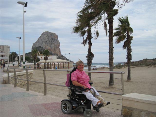 Marie wandelt met haar elektrische rolstoel langs het strand.
